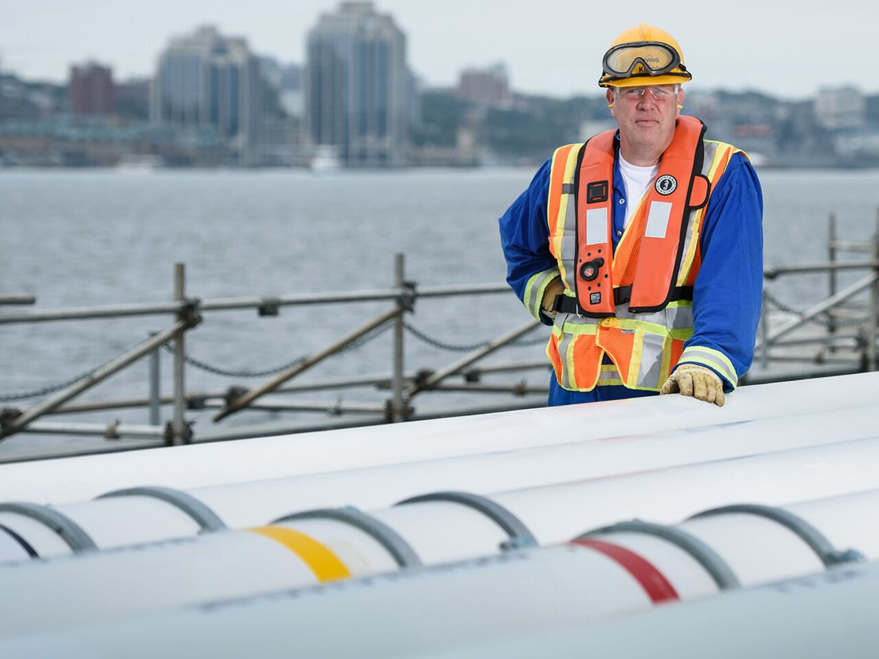 """alt=""""oil shipping worker posing with large pipes"""""""